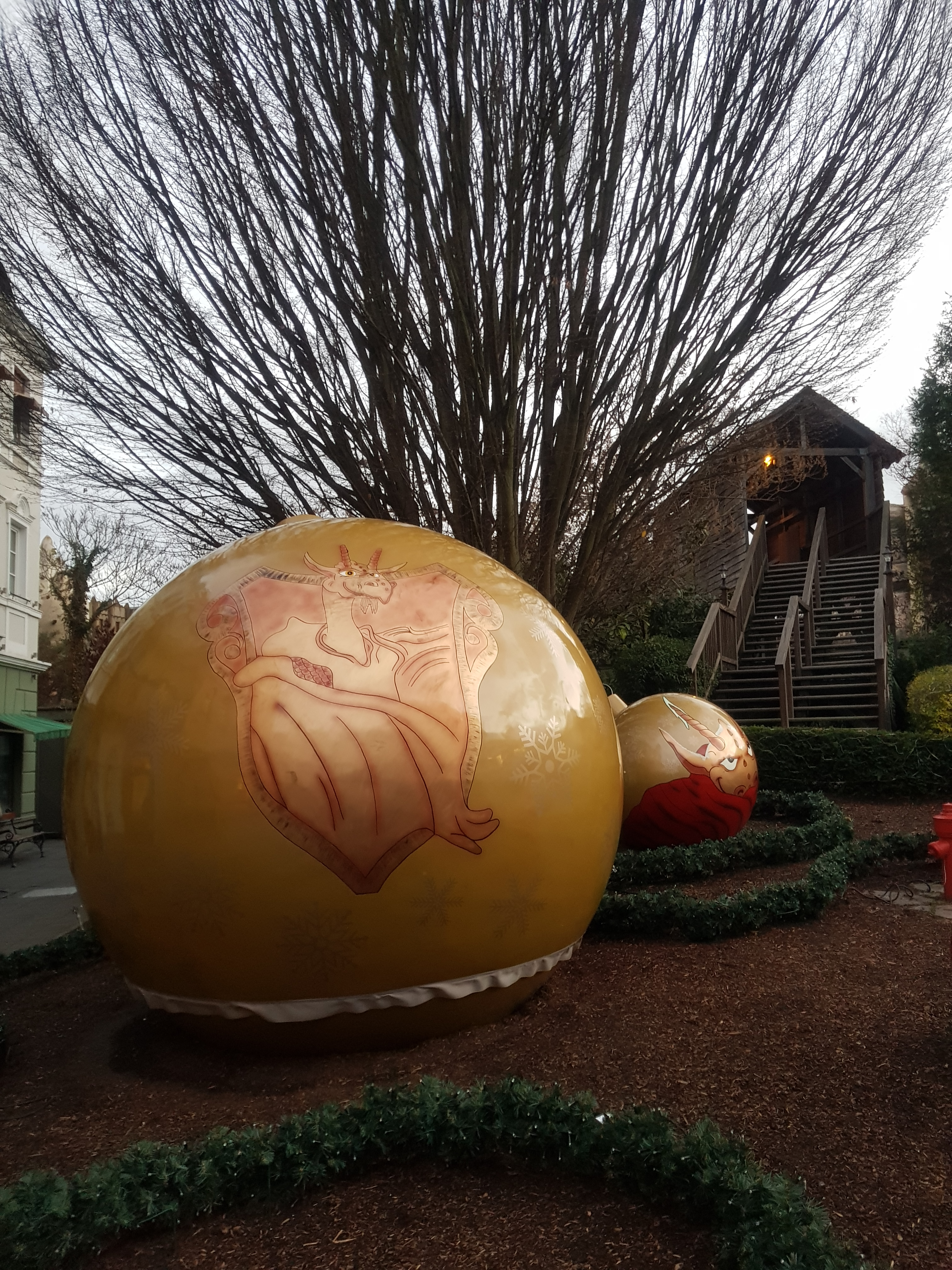 Reuze goudkleurige kerstbal op de grond met een afbeelding van een draak