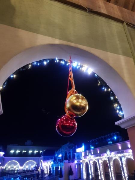 grote kerstballen opgehangen in een stenen boogje met uitkijk op de ijsbaan